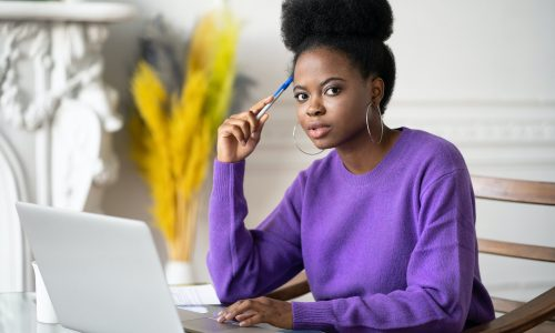 Afro student woman with afro hairstyle looking at camera, preparing for exam online on laptop.