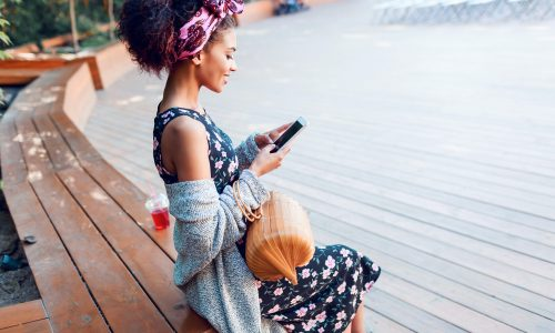Happy black woman with stylish Afro hairstyle using mobile phone.