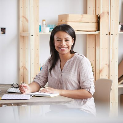 smiling-mixed-race-woman-at-desk-PY2ZLH6.jpg